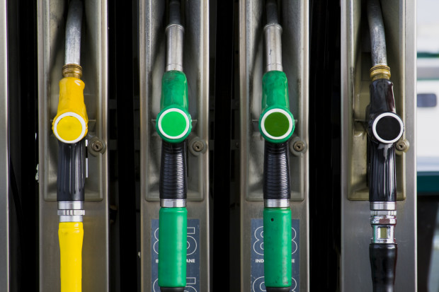 4 gas pump nozzles at a gas station